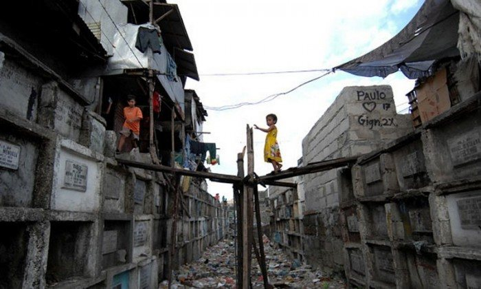 A child walks on a makeshift bridge between shanty homes built on top of banks of tombs inside the north Manila cemetery. (Photo: Noel Celis / AFP / Getty Images)